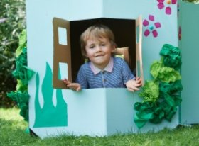 child in cardboard house