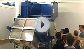 Girl lifting cardboard boxes into an auger crusher compactor