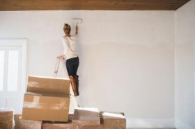Young woman decorating new home - Cultura/Hugh Whitaker/Riser/Getty Images